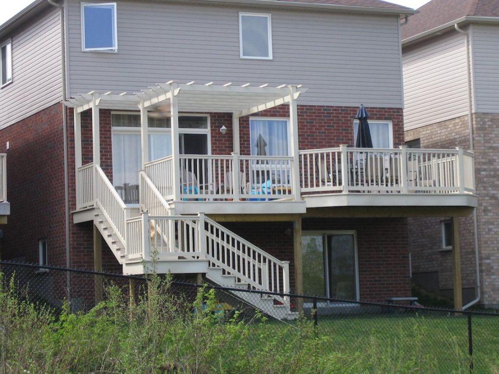 White Vinyl Porch Railing With Custom Pergola Installation on House